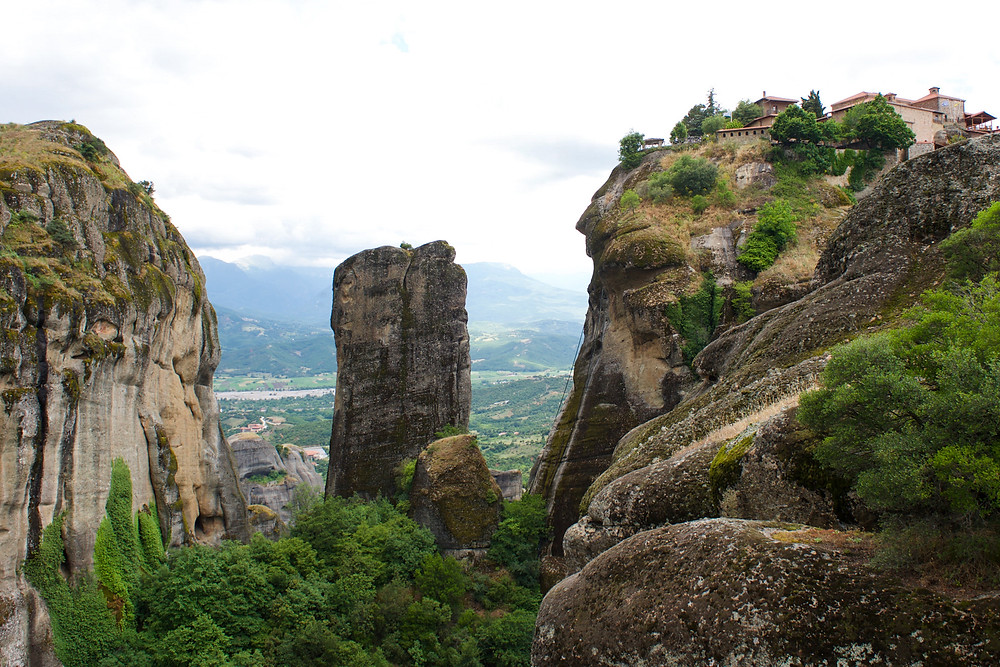 Three natural pillars of rock standing among greenery, one with a monastery atop it in Meteora, Greece
