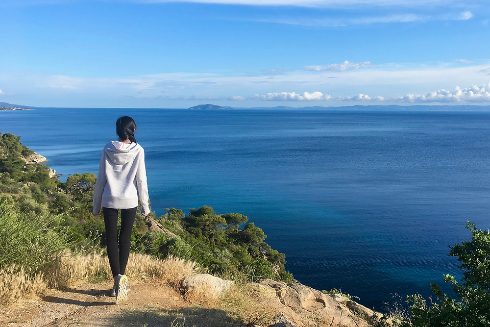 Eryn stands at the edge of a cliff and looks out to the Aegean Sea in Greece.