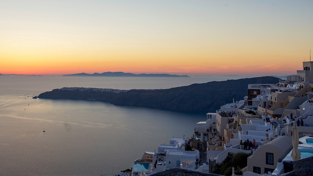 Buildings of Oia village in front of a peninsula under a sky turned orange by the sunset