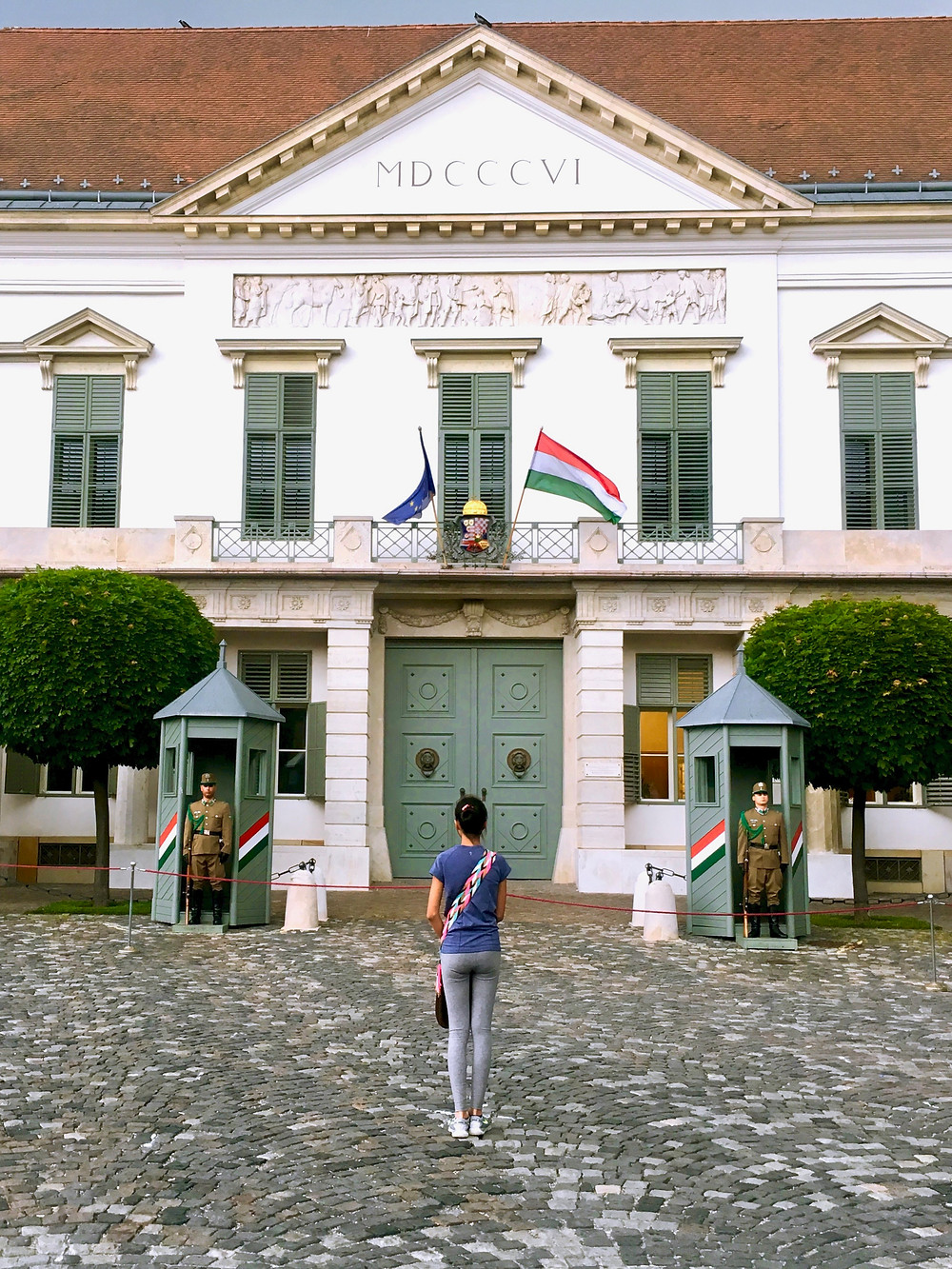 Eryn standing in front of the doors of Sándor Palace with its red roof and green windows, doors, and guard posts in Budapest