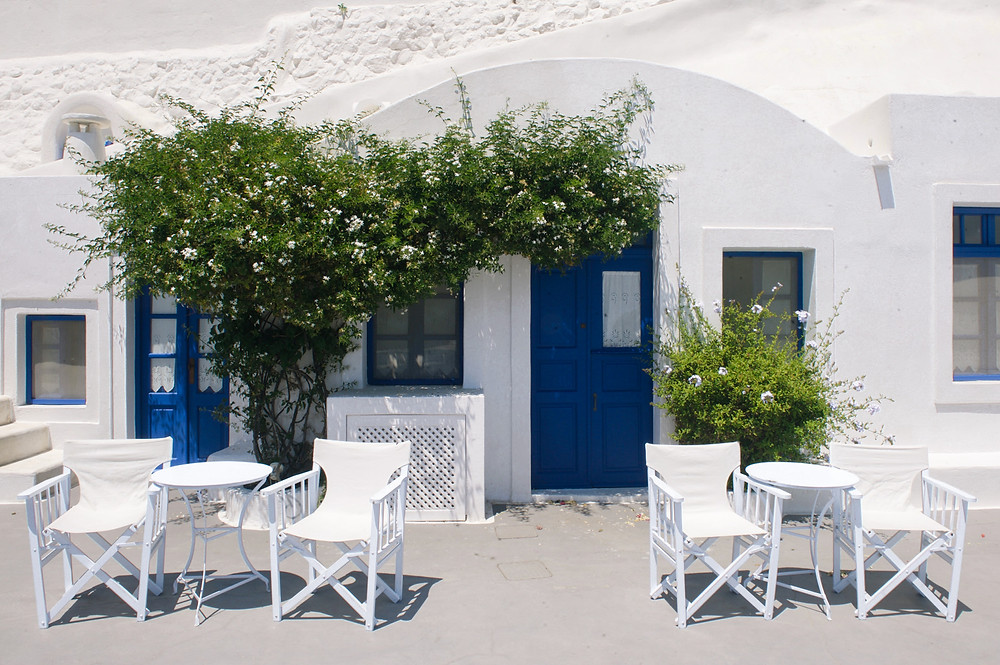 Seats and tables outside traditional whitewashed cave rooms in Aghios Artemios, Santorini, Greece