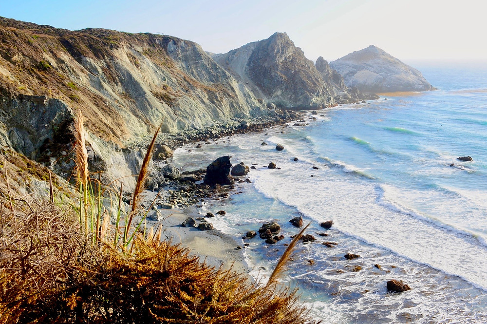 A rocky coastline by light blue waves and hills continuing into the distance along the Pacific Coast Highway
