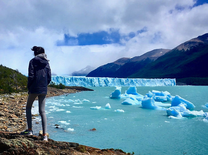 Eryn stands at the banks of Lago Argentino and looks out to the Perito Moreno glacier in the distance