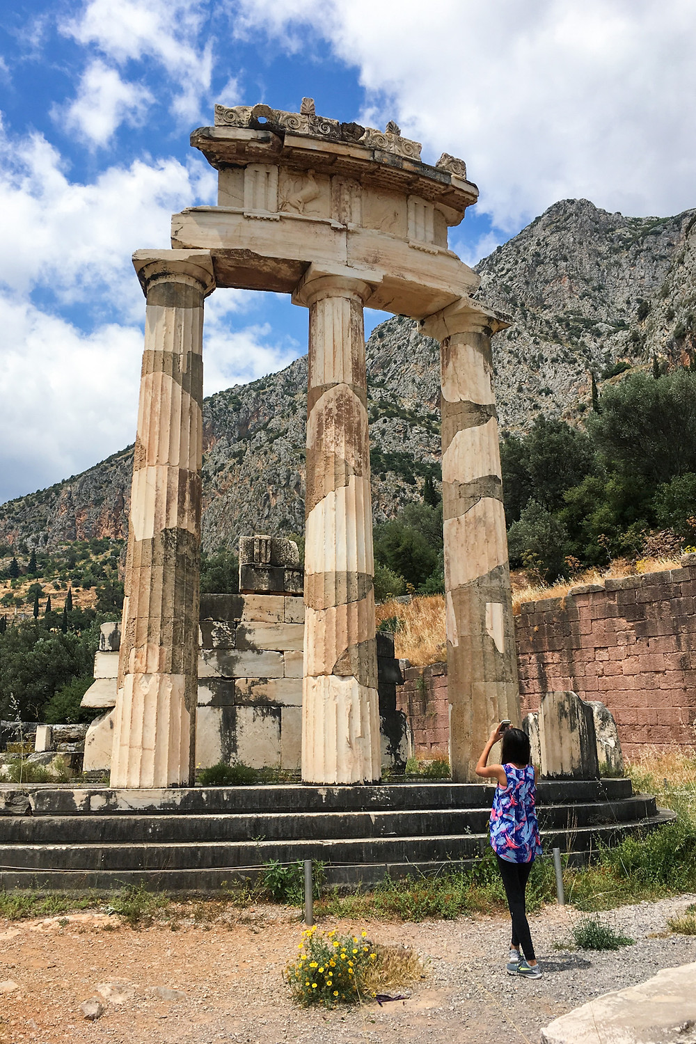 Eryn stands beneath the three standing pillars of the tholos to take a photo