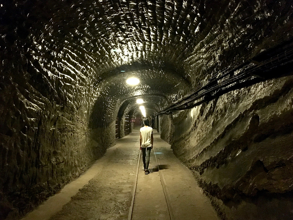 Eryn walks through a tunnel with walls of salt and railroad tracks on the ground in the Wieliczka Salt Mine