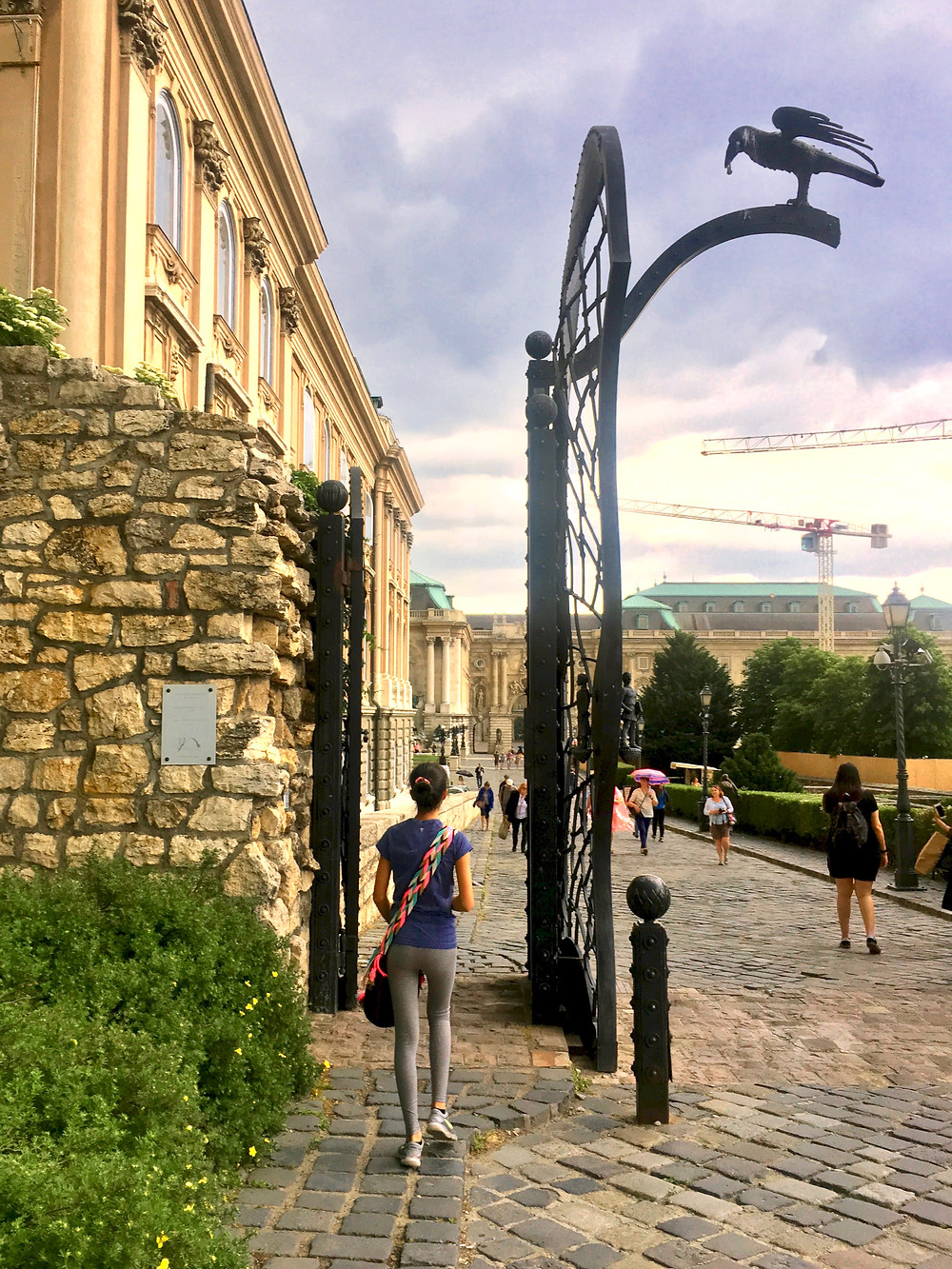 Eryn walking through a black gate with a metal crow perched on it to enter the Buda Castle complex in Budapest, Hungary