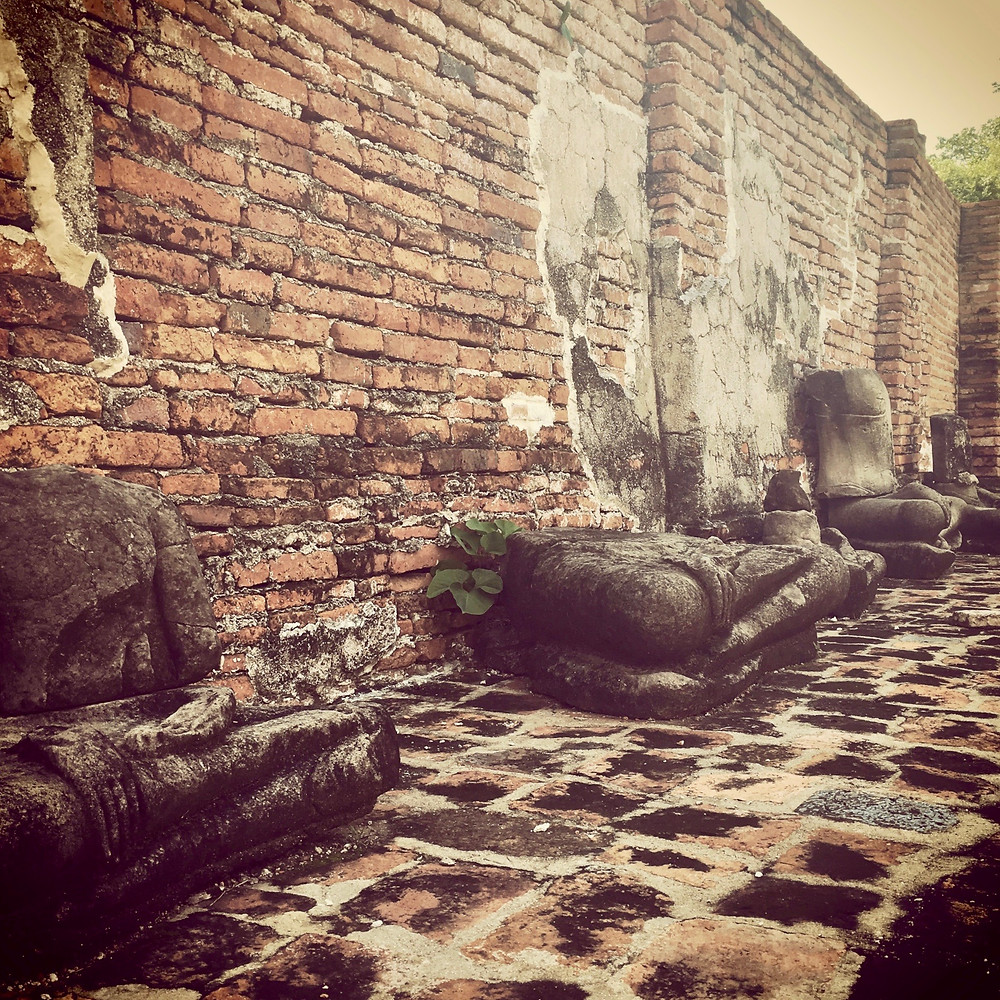 Fragments of Buddha statues lined across an ancient brick wall in Wat Mahathat of Ayutthaya, Thailand