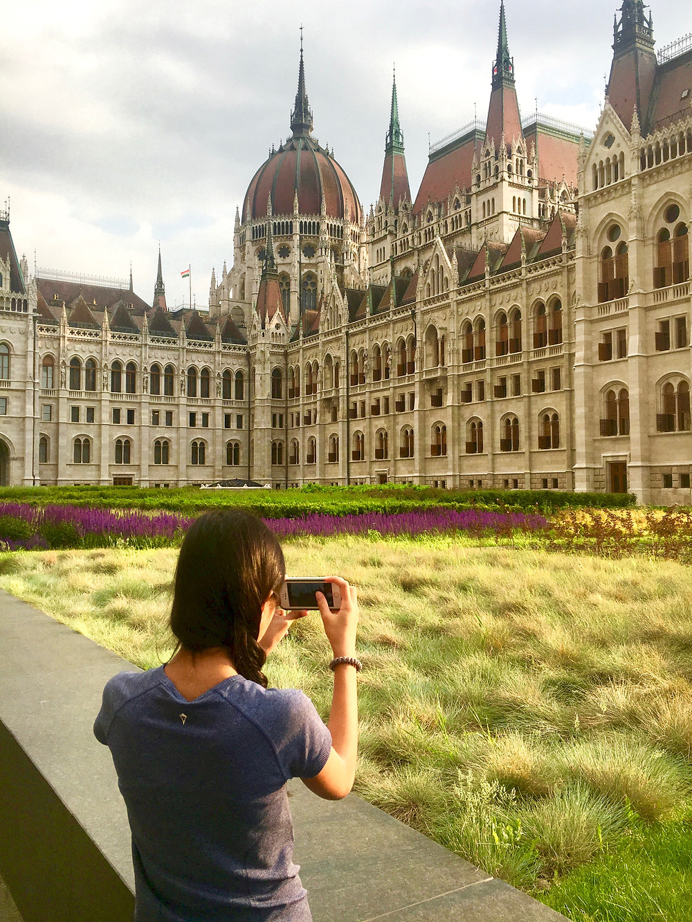 Eryn taking a photo of the Hungarian Parliament Building in front of its gardens under a cloudy sky in Budapest