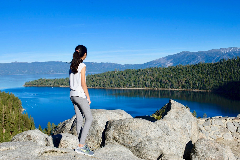 Eryn looking out to a blue sky above mountains, green forests, and the blue waters of Lake Tahoe