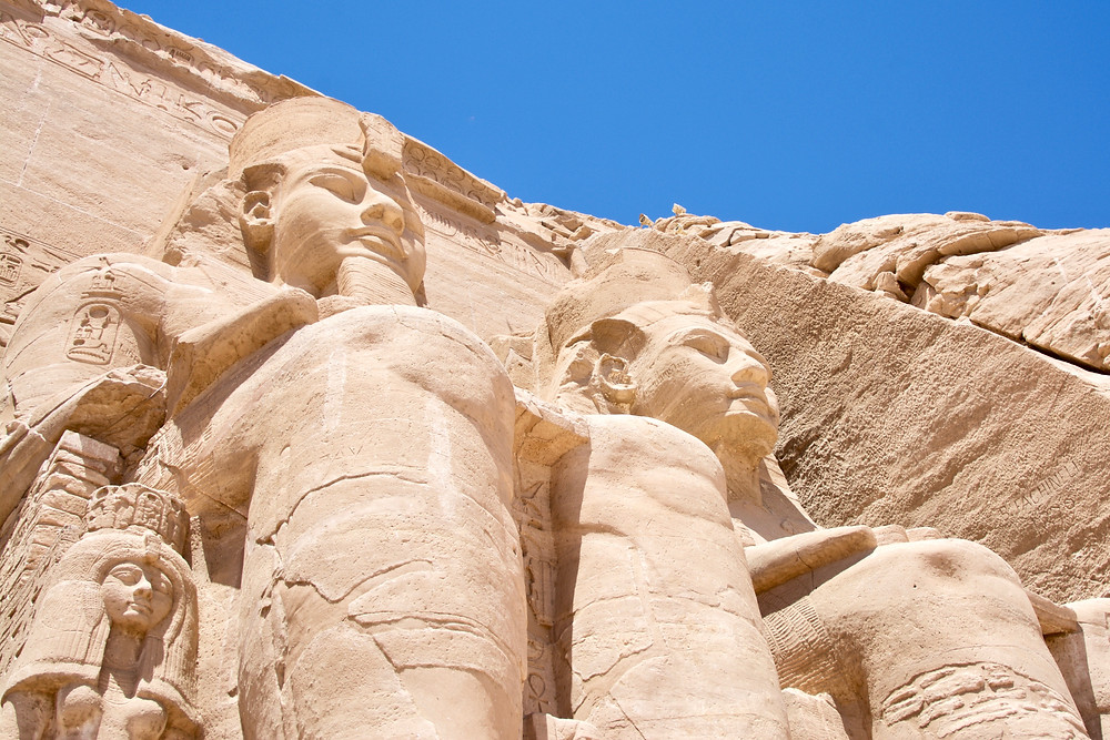Looking up at the massive statues carved into the cliff face of Abu Simbel against a bright blue sky in Egypt
