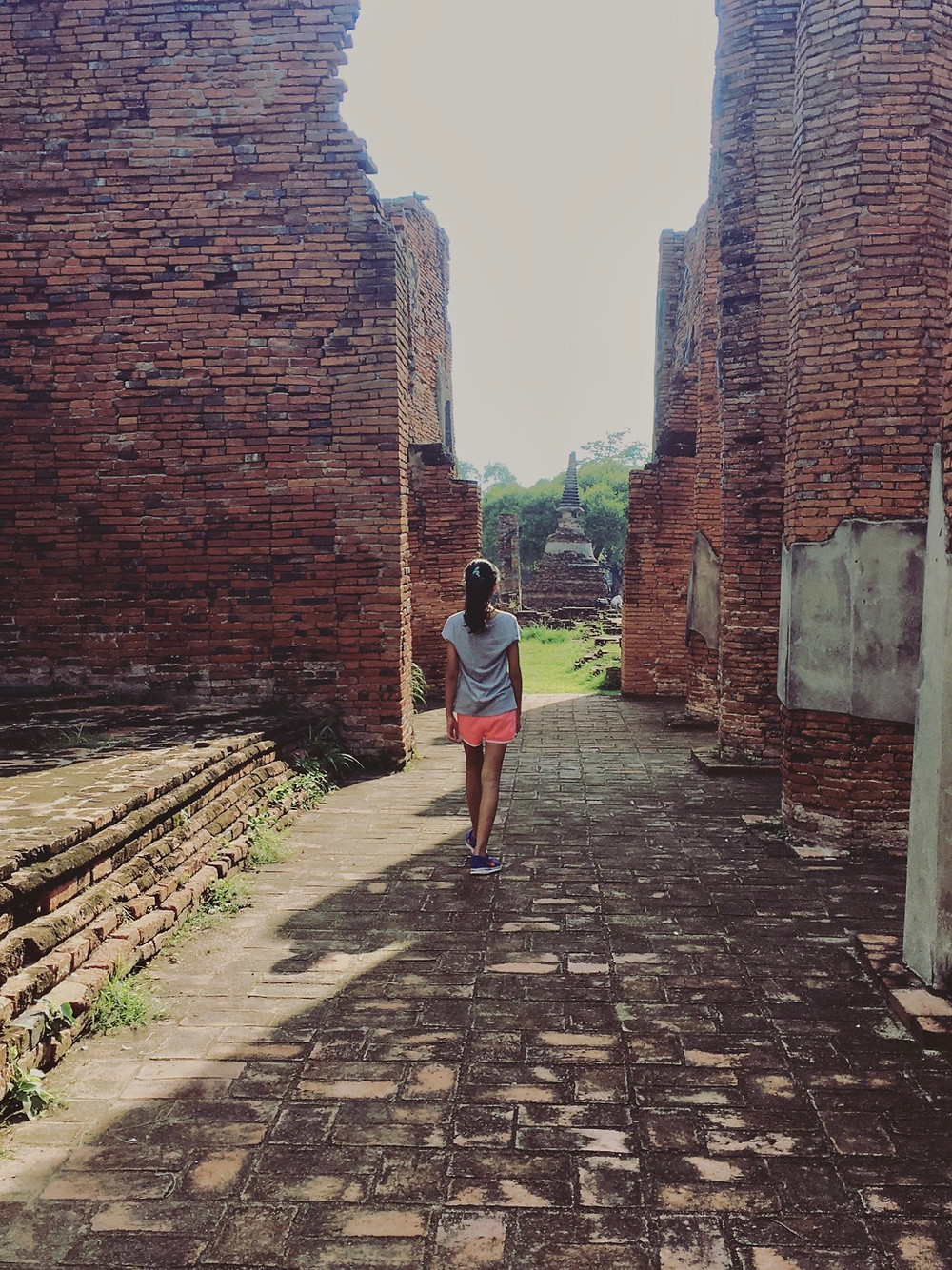Eryn walking past brick wall ruins in the ancient city of Ayutthaya, Thailand