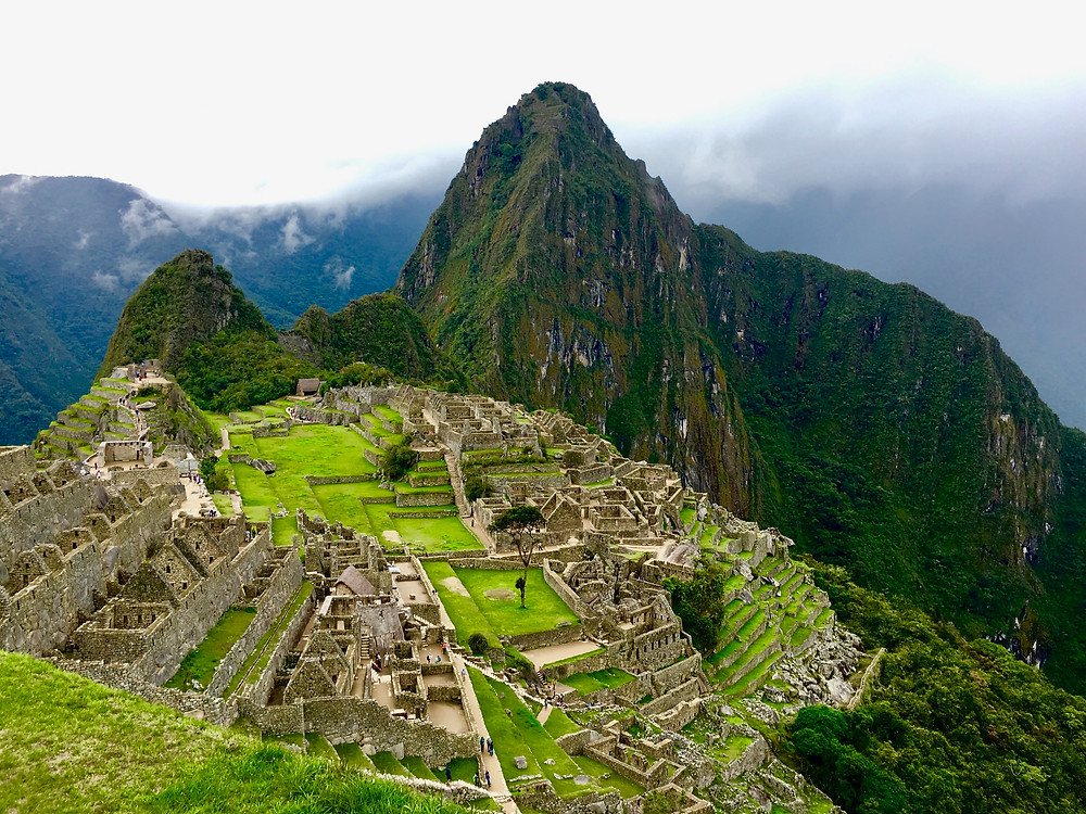 A view of the ruins of Machu Picchu on terraced hills and the iconic Peruvian mountains in the distance