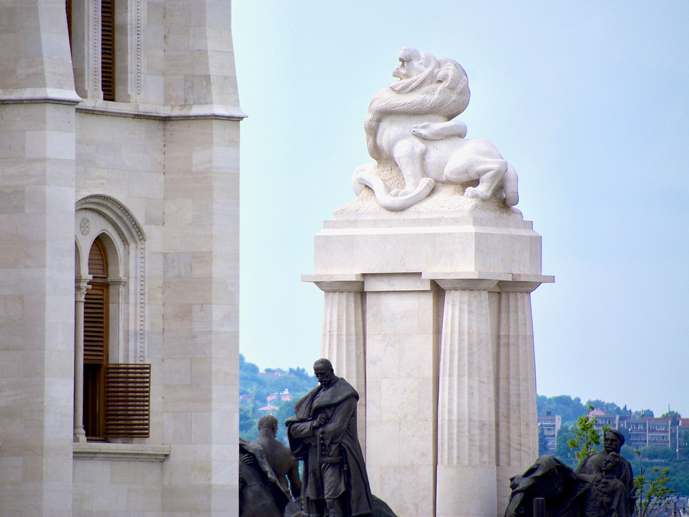 The top of the István Tisza Monument feature a stone lion bitten by a snake behind the Hungarian Parliament Building