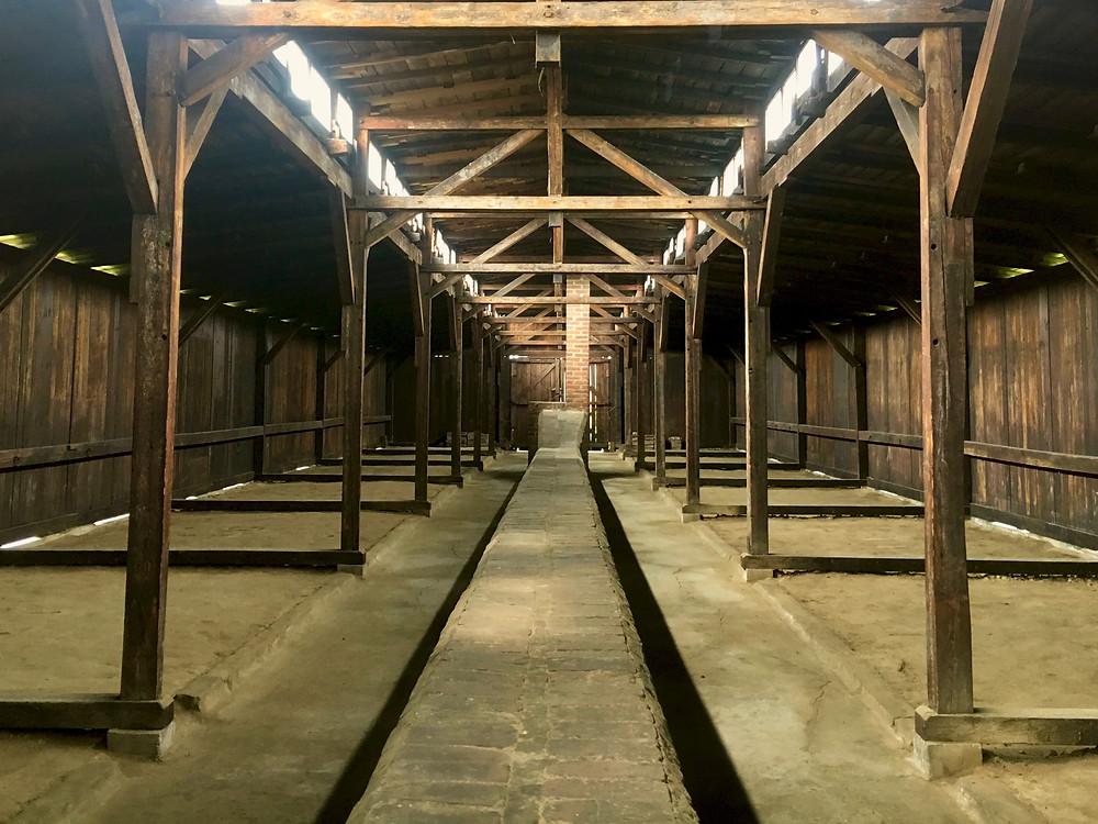 The interior of a wooden barrack at Auschwitz II with dirt floors and a brick fireplace column running through the center
