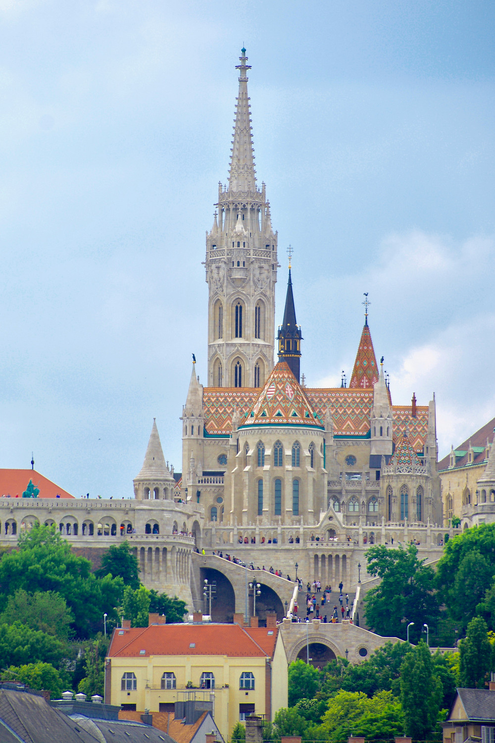 The colorful orange spires of the Matthias Church by the Fisherman's Bastion in Budapest, Hungary surrounded by greenery under a bright blue sky