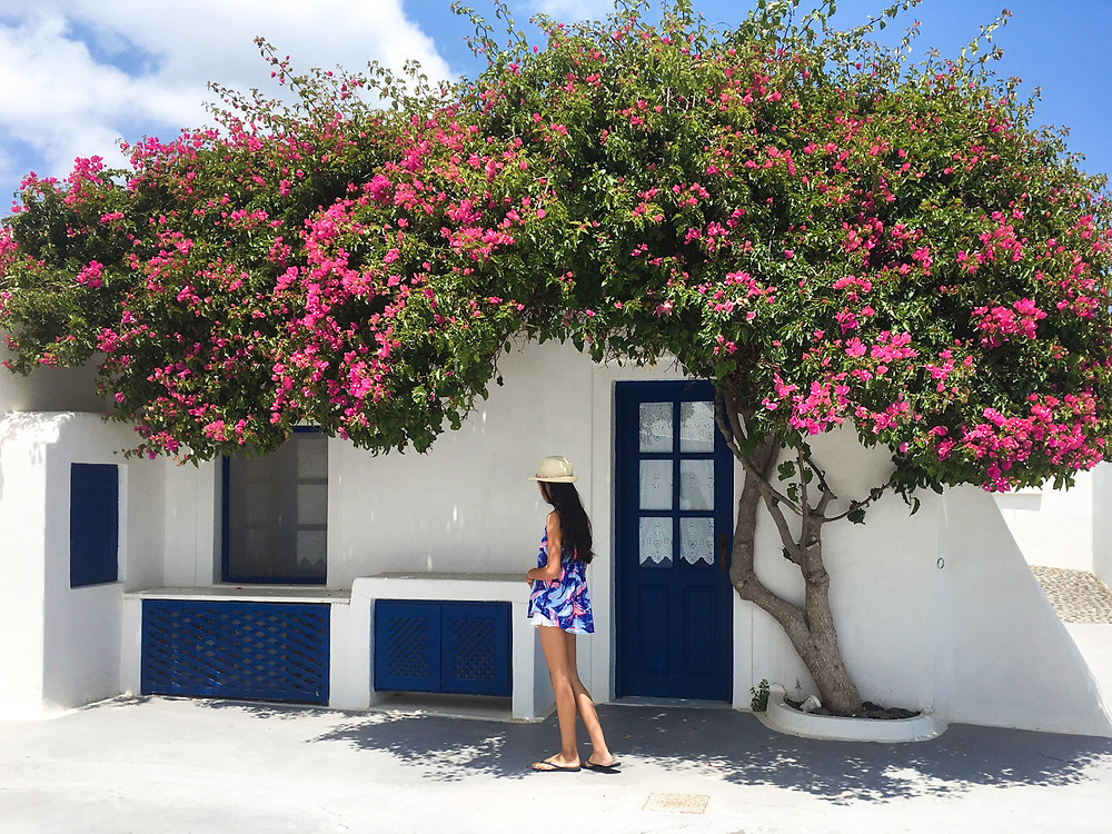 Eryn stands beside the outside of a whitewashed cave house in Aghios Artemios under a tree with pink flowers