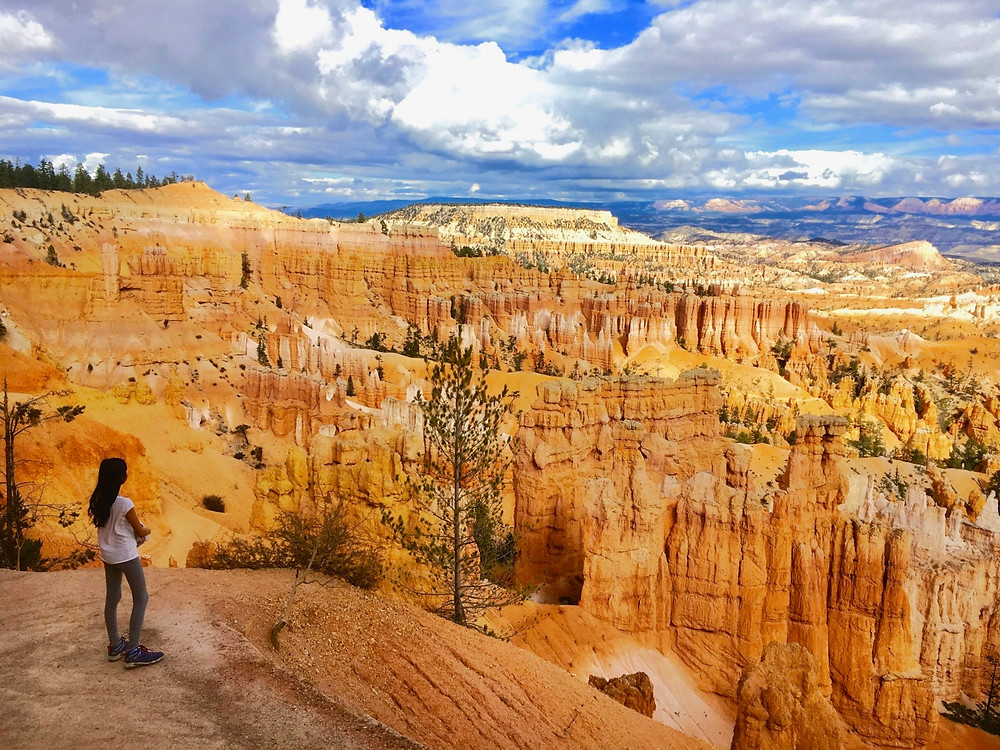 Eryn looking out to the orange canyon and rock formations under a bright blue cloudy sky in Bryce Canyon National Park