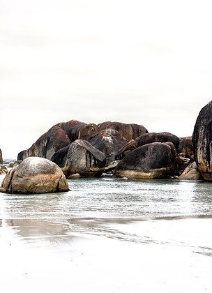 Fine Art designer print titled Boulder. Large black boulders in pale neutral ocean with hints of orange and patches of white.