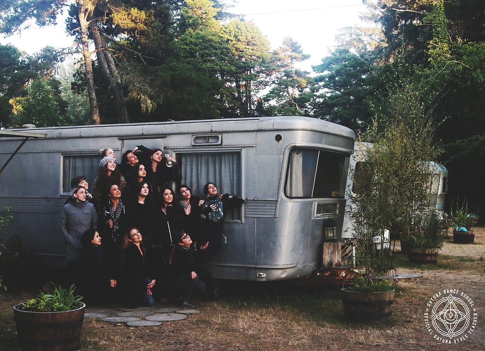 Group of belly dance teachers standing in front of a vintage travel trailer, surrounded by trees and a bright skyline