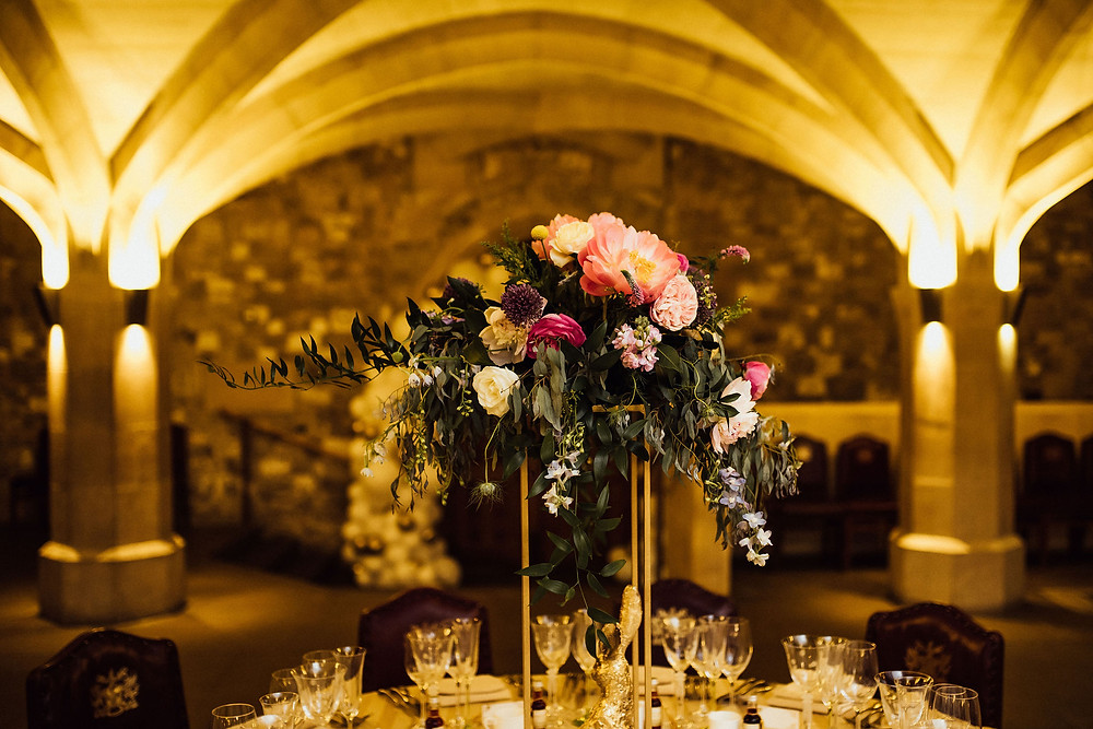 Wedding table at London Guildhall decorated with tall gold metal stand and wedding flower arrangement.