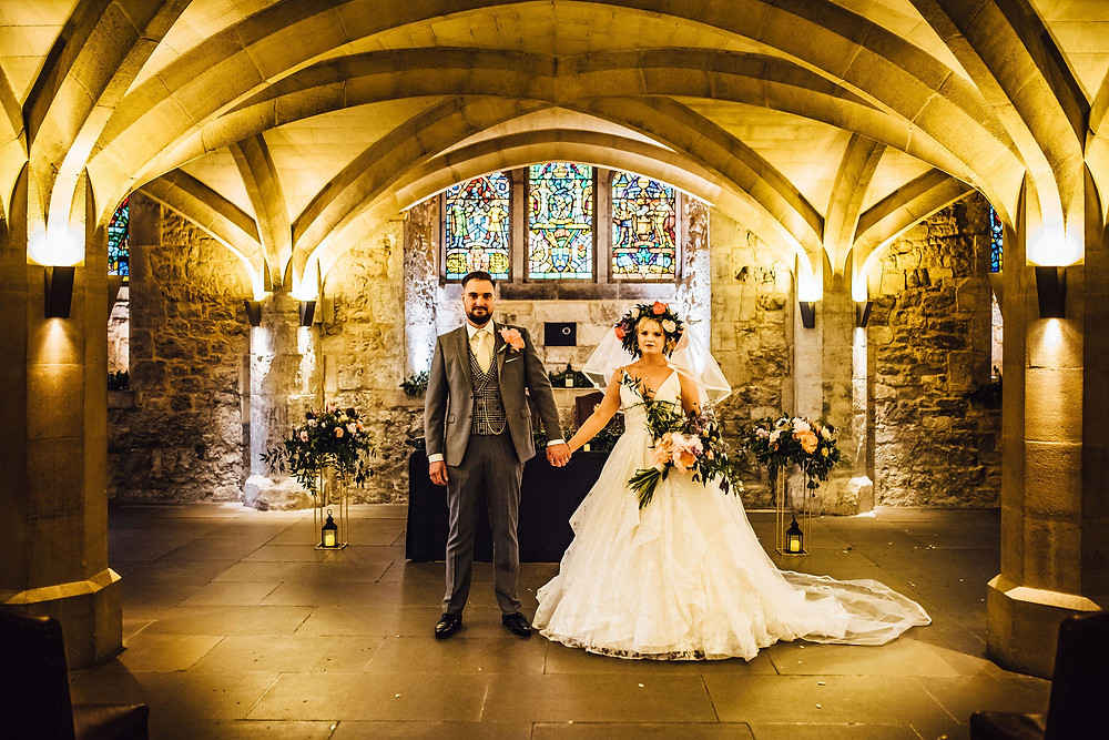 Bride in flower crown marries groom in houndstooth waistcoat at London Guildhall civil ceremony with tall metal flower stands either side of ceremony table.