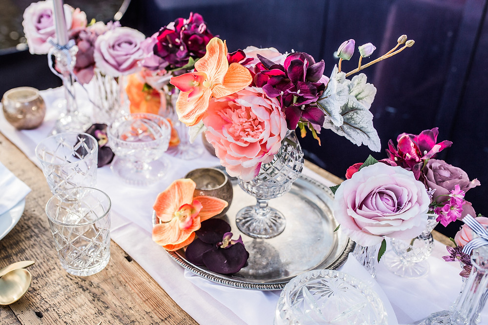 Antique silver drinks tray and floral arrangements on rustic handmade wood trestle table.