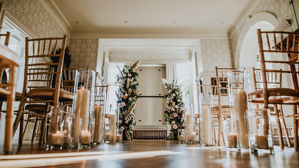Oversized floor lanterns and candle vases ceremony arch floral installation Chippenham Park Wedding