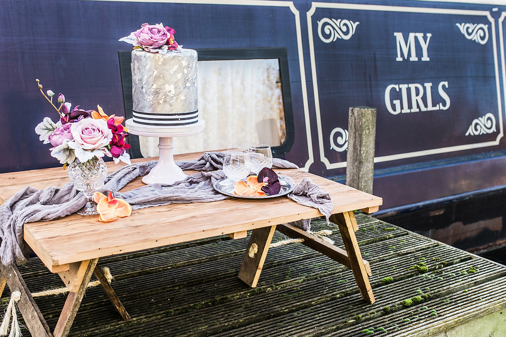 Contemporary wedding cake table styling with floral arrangements and muslin table runner, next to My Girls narrowboat on the Heybridge Basin.