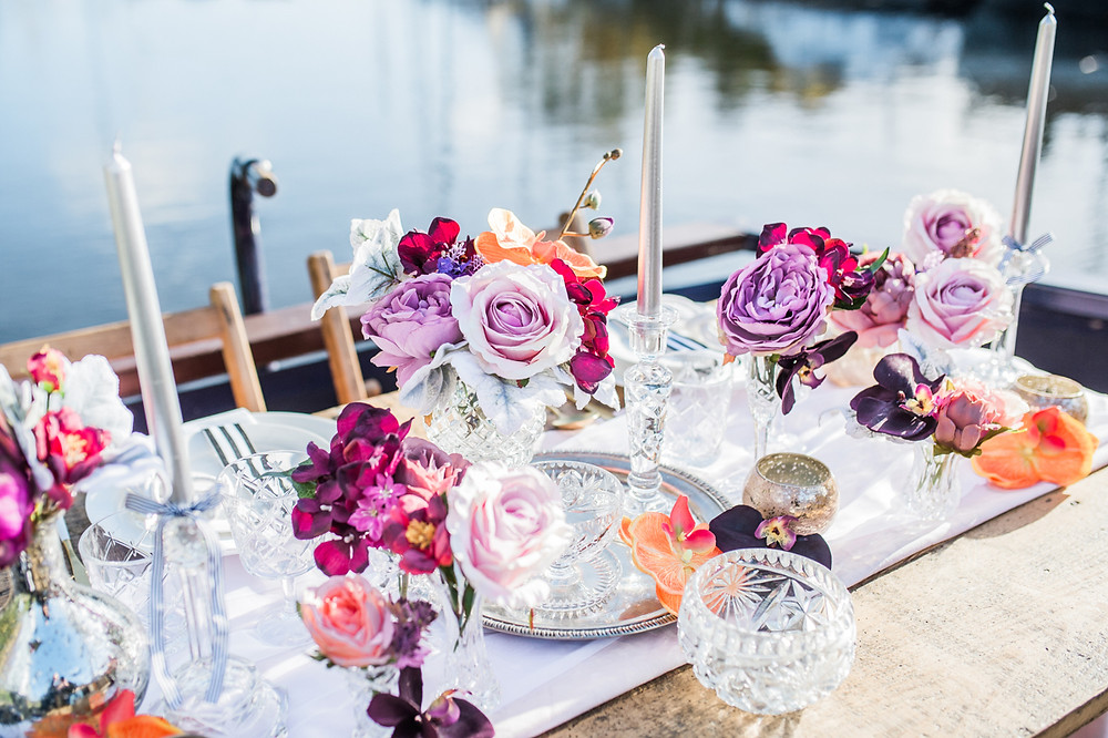Rustic trestle sweetheart table laid with a table runner, cut glass, crystal and bud vases of bright and beautiful artificial arrangements,