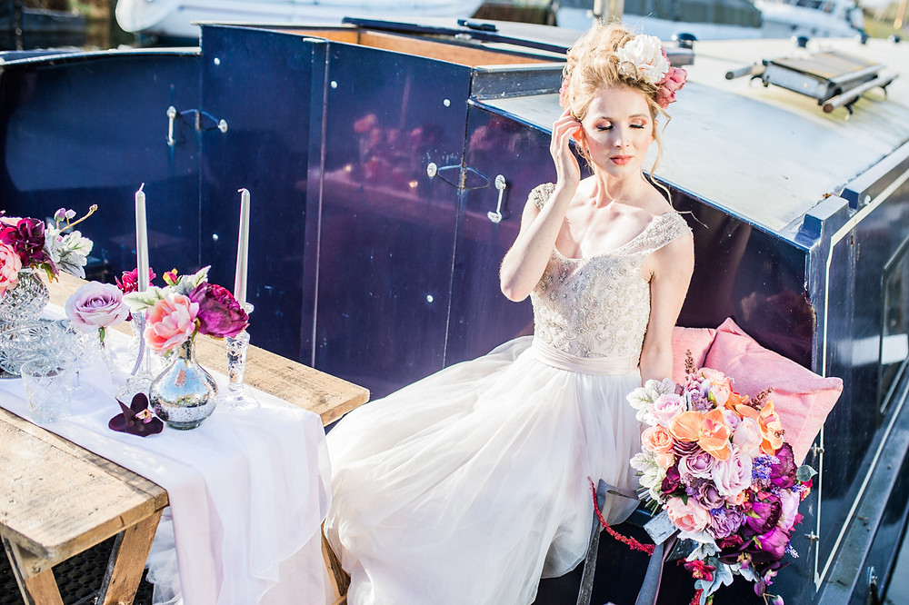 Contemporary bride marrying outdoors on a narrowboat on the British canal waterways. Colour bock wedding bouquet created by Miss Fleur Floral. Dresses by Bridal Reloved Maldon