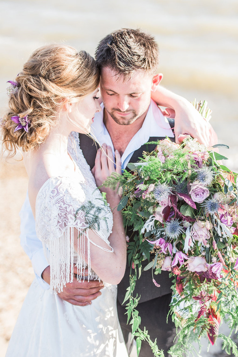 Boho bride and casual groom with oversized bouquet on english beach