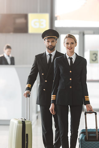 happy male and female pilots walking by