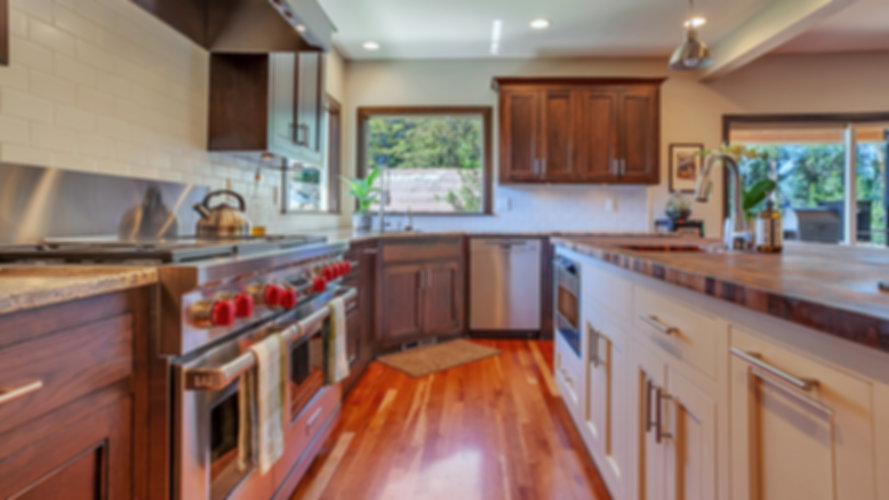 Stain kitchen with butcher block countertop on the island. Wolf appliances. Custom cabinets. Hardwood floors.