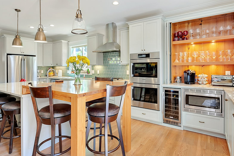 Recessed panel doors, waterfall table, wine fridge, wine rack, quartz countertop, painted cabinets, range hood, recessed shelving.