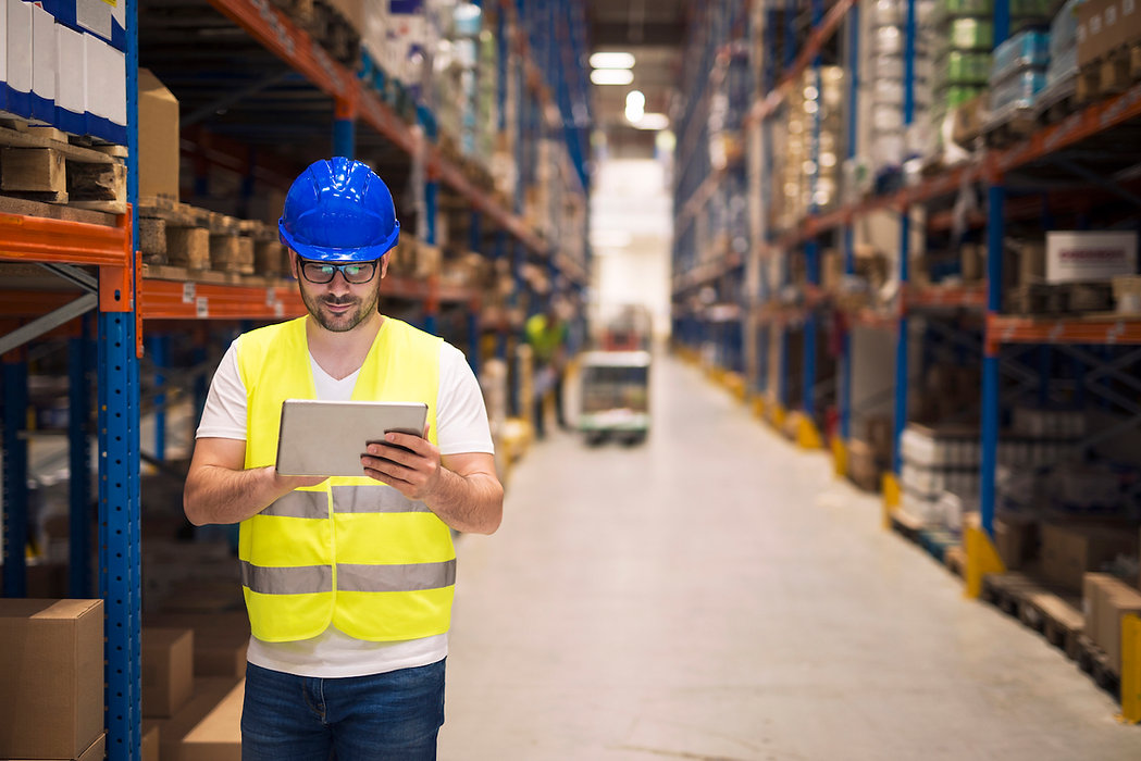 warehouse-worker-checking-inventory-his-tablet-while-walking-large-storage-department-with