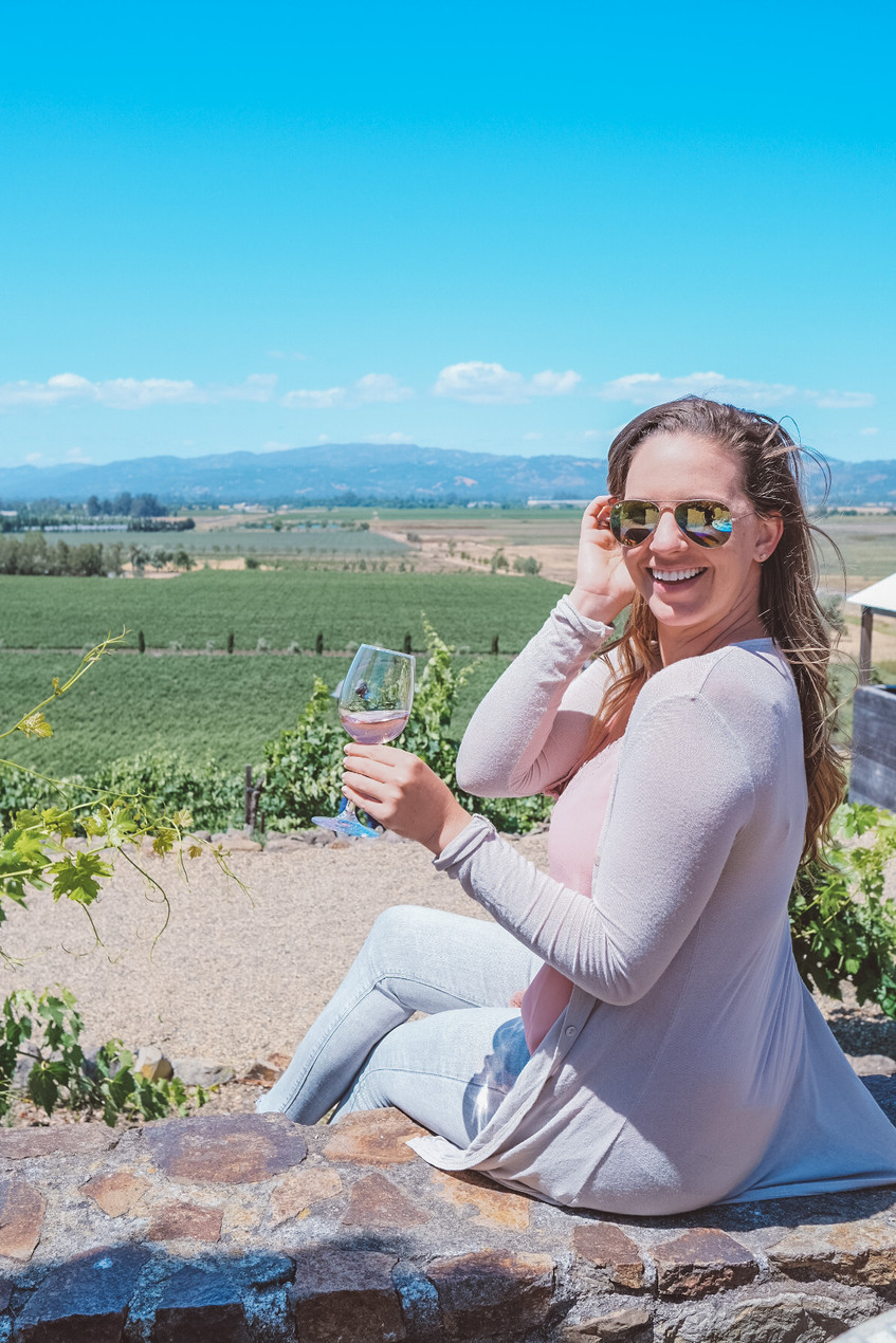 Young, blonde woman wine tasting in California. Beautiful Wine Country views.