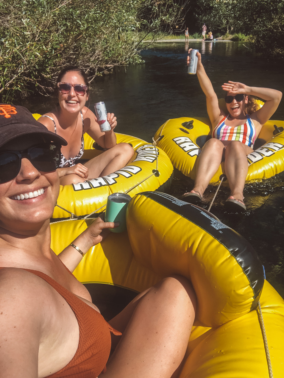 three girlfriends floating in tubes on the Russian River in California