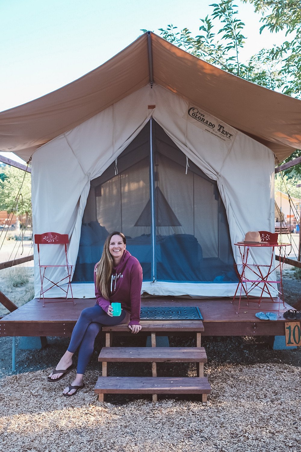 blonde woman sitting outside of a luxury glamping tent in leggings and a hoodie in California