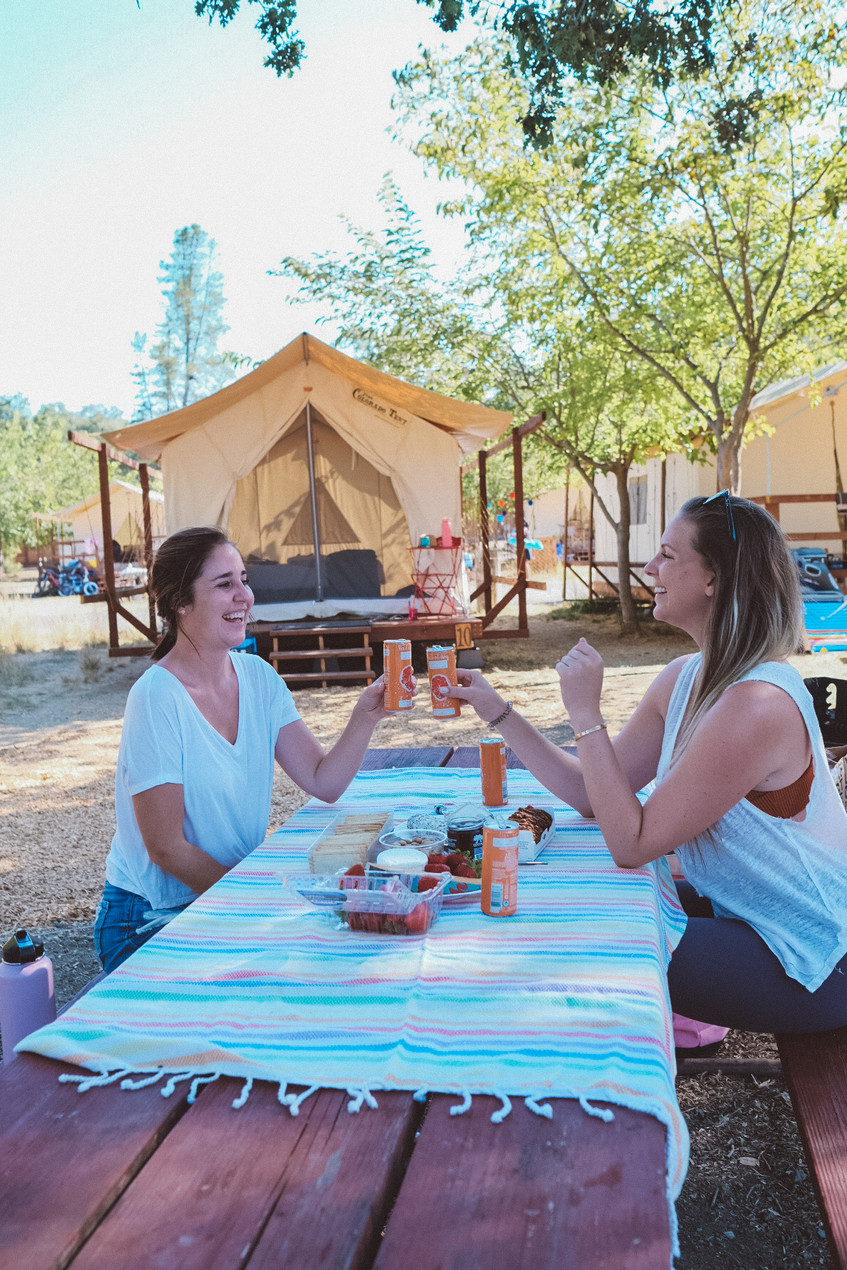 two women enjoying wine and cheeses at a camp ground in California