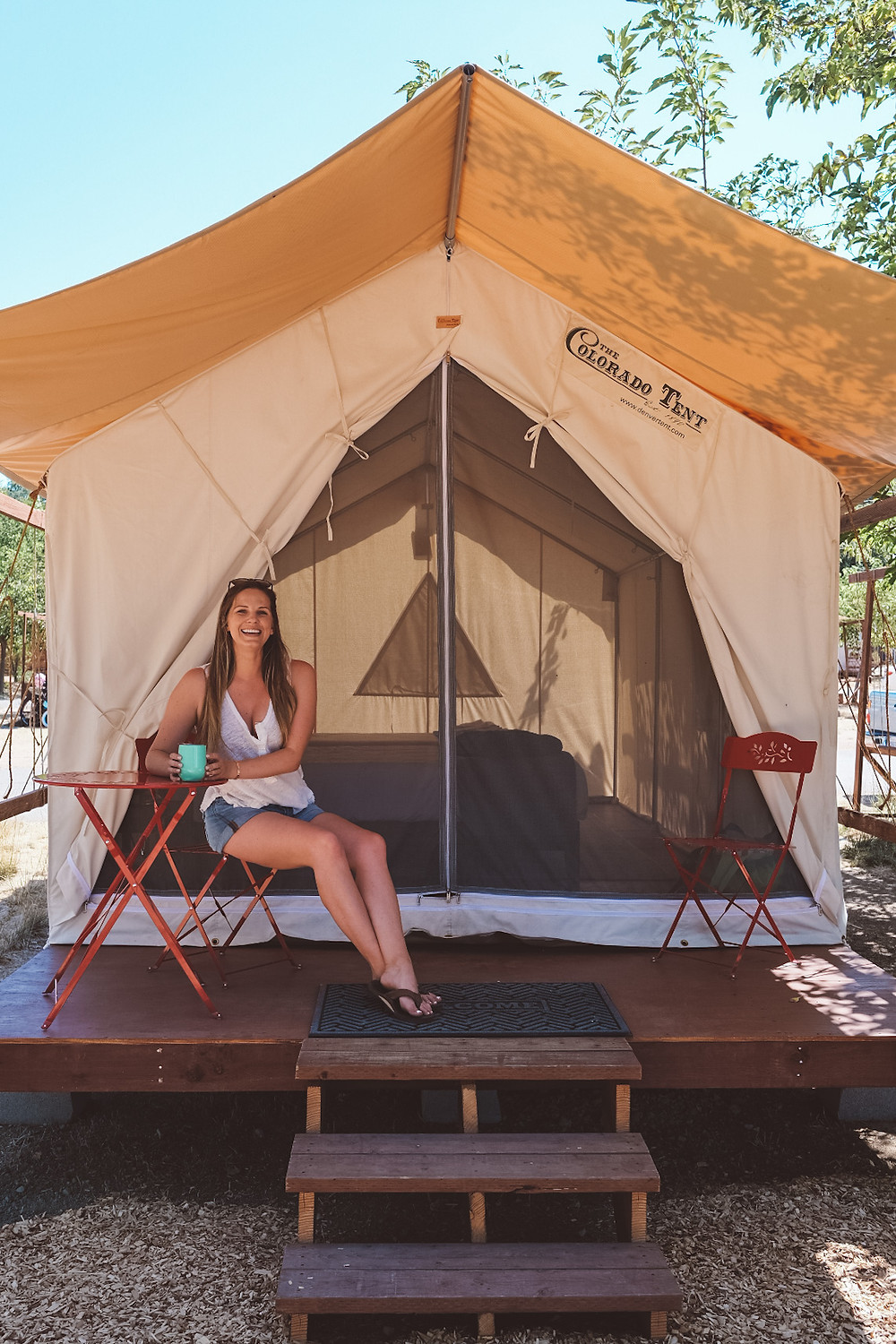 woman sitting outside of a luxury tent in California