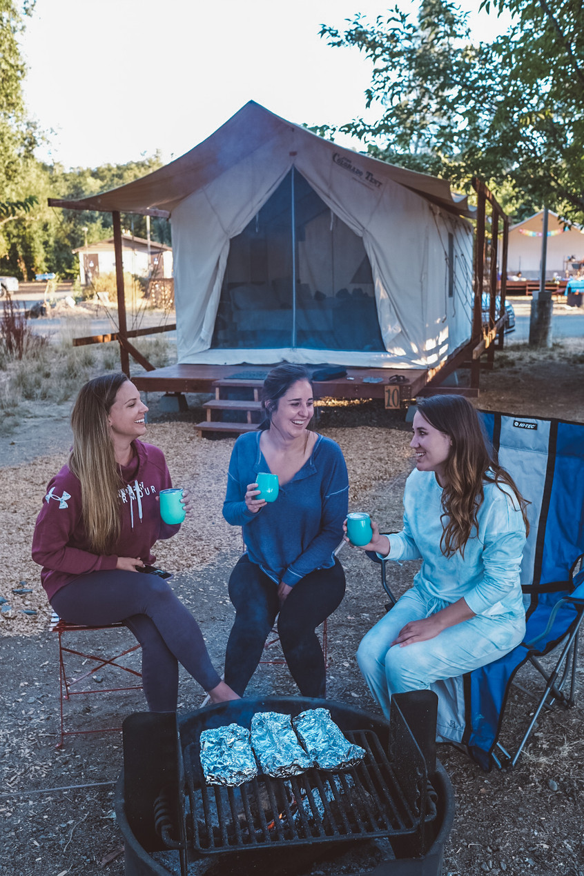 girlfriends enjoying wine by a campfire at a camp ground in California