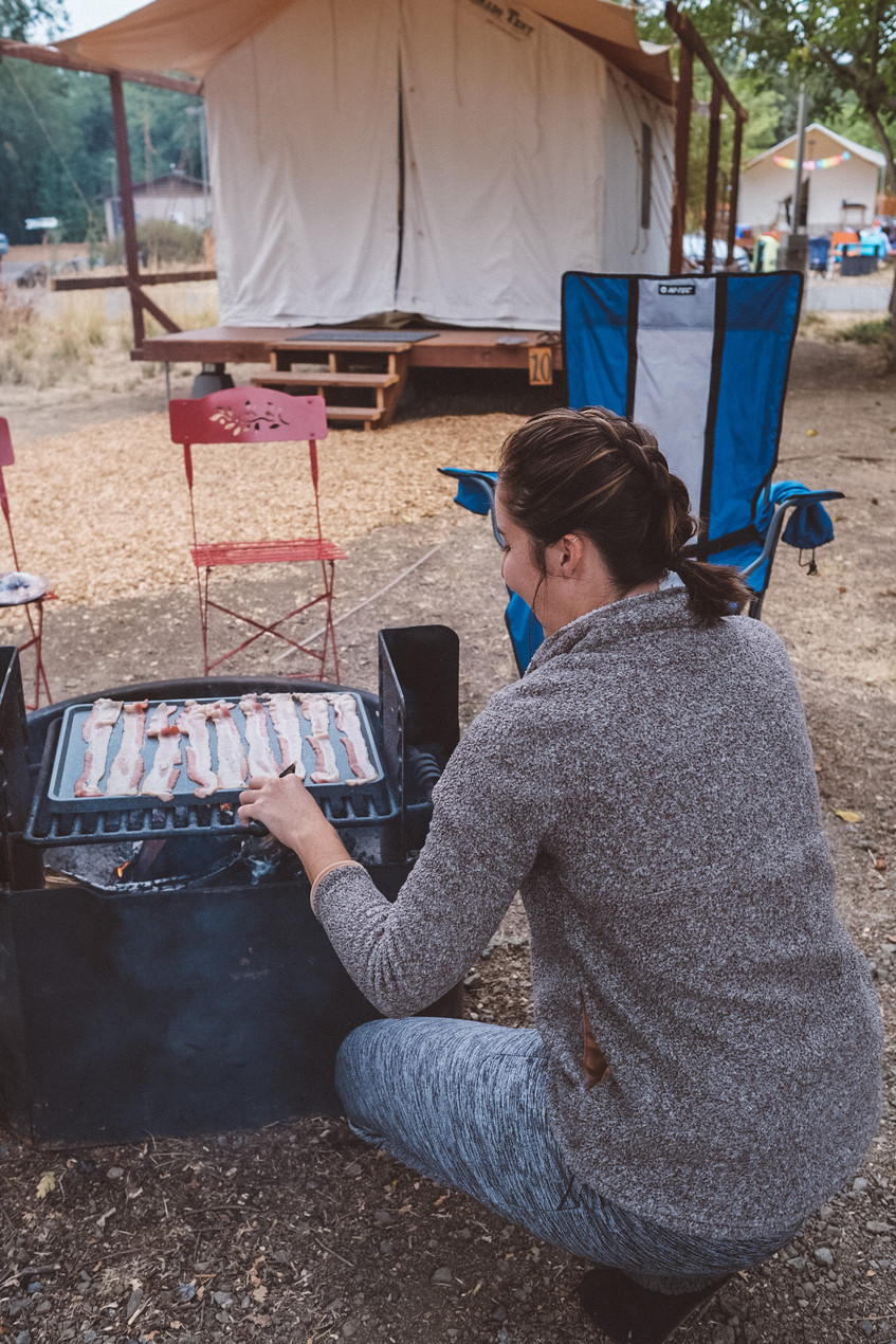 women cooking bacon over a woof fire while camping in California