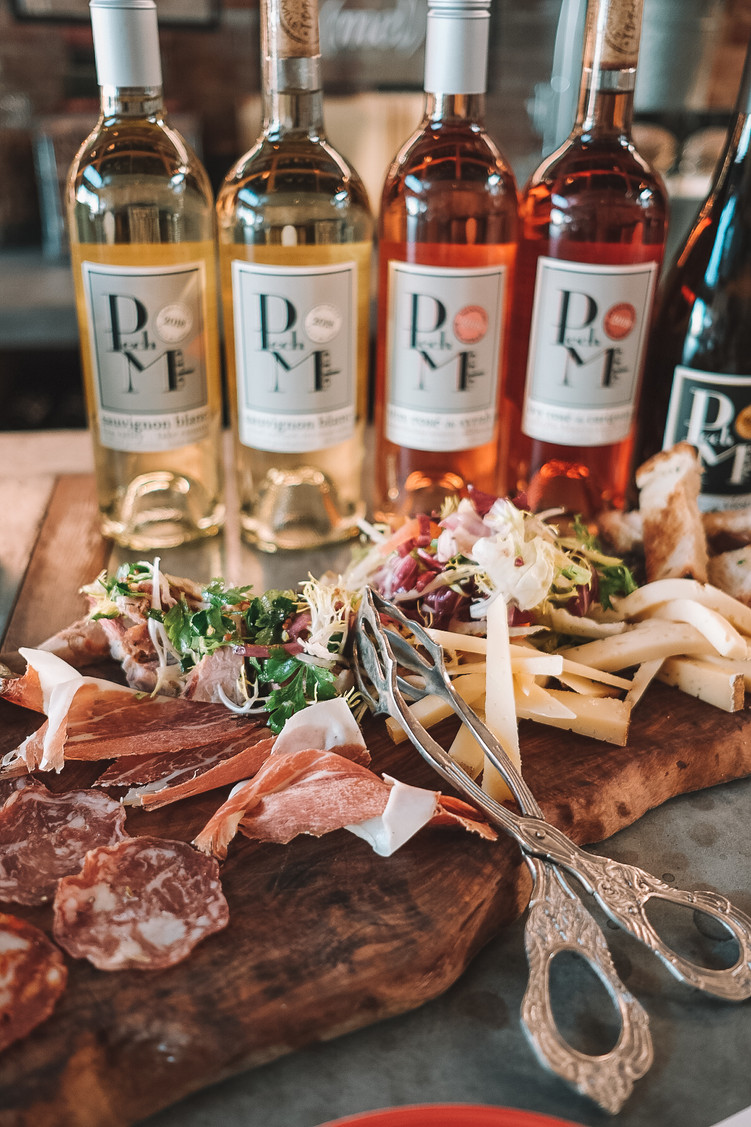 cheese and charcuterie board with white wine and rose bottles at Pech Merle Winery in Geyserville, California