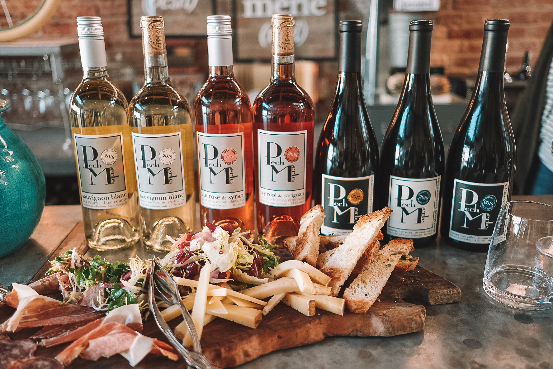 Pech Merle wine and wine bottles lined up behind a delicious cheese and charcuterie board
