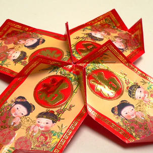 Now place four wrappers in a circle, and staple the folded corners together to join them up.  Make sure the design on each red packet is the right way up.  This will form the top of the lantern.