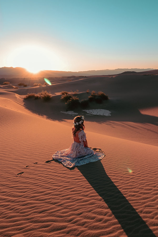 Girl sitting on top of sand dunes at sunset with pretty flowy dress in Death Valley National Park, California. Photo by Daniela Blagoeva travel vacation portrait photographer based in Las Vegas, NV, Sofia Bulgaria, available for travel worldwide