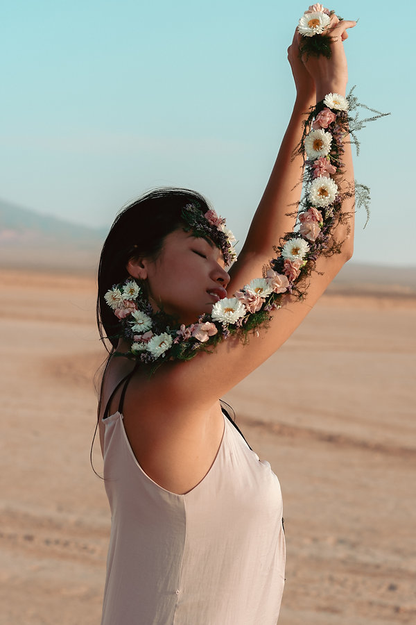 Boho style desert portrait photoshoot with beautiful girl and wearable flowers by WildfleurDesigns, Jean Dry Lake Bed, Las Vegas, NV. Photo by Daniela Blagoeva portrait fashion photographer based in Las Vegas, NV and worldwide