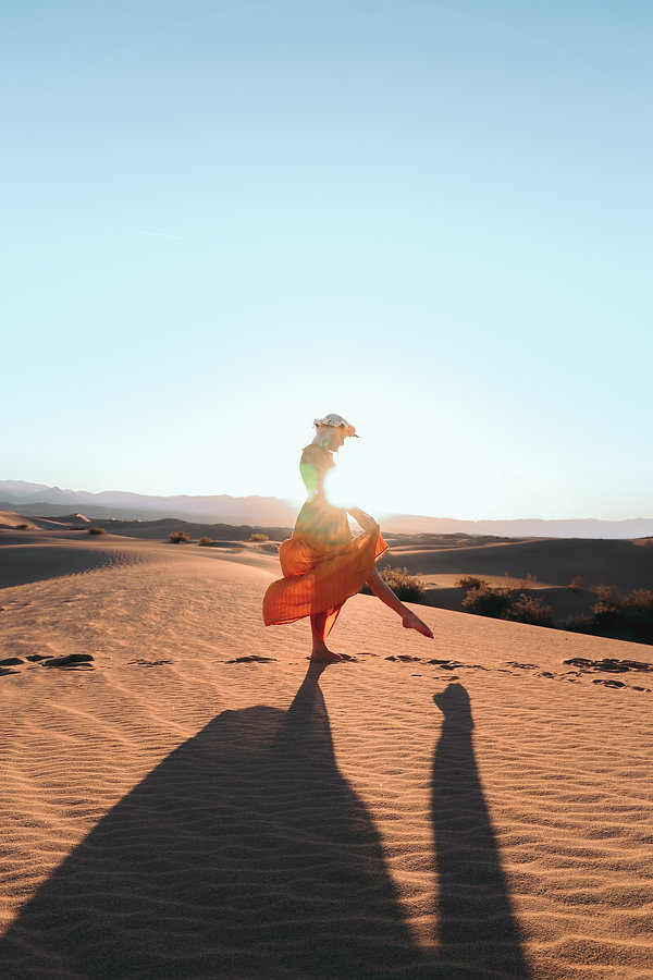 Girl in flowy dress sun glow travel vacation Instagram photoshoot in Death Valley Sand Dunes, CA. Photo by Daniela Blagoeva travel destination photographer based in Las Vegas, Sofia Bulgaria, available for travel worldwide