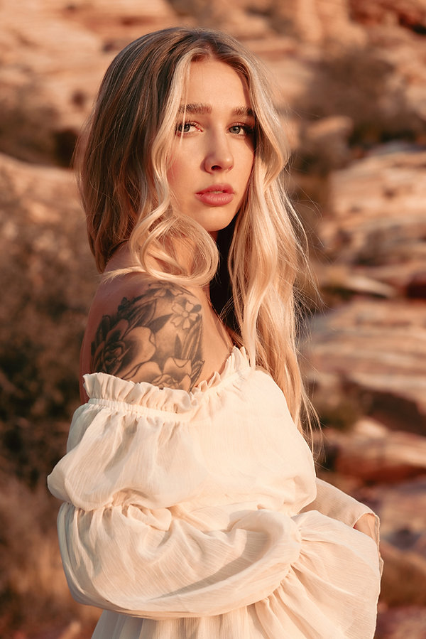 Blond model wearing off the shoulder white bohemiean dress outdoor desert closeup portrait photoshoot in Red Rock Canyon, Las Vegas, NV. Photo by Daniela Blagoeva portrait and fashion photographer based in Las Vegas, NV and Sofia, Bulgaria, available worldwide
