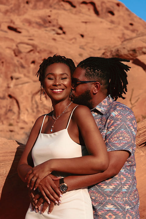 Woman in love smiling as man hugs and kisses her neck engagement photos in the dessert. Photo by Daniela Blagoeva engagement portrait photographer based in Las Vegas, NV, Sofia Bulgaria, availabale worldwide